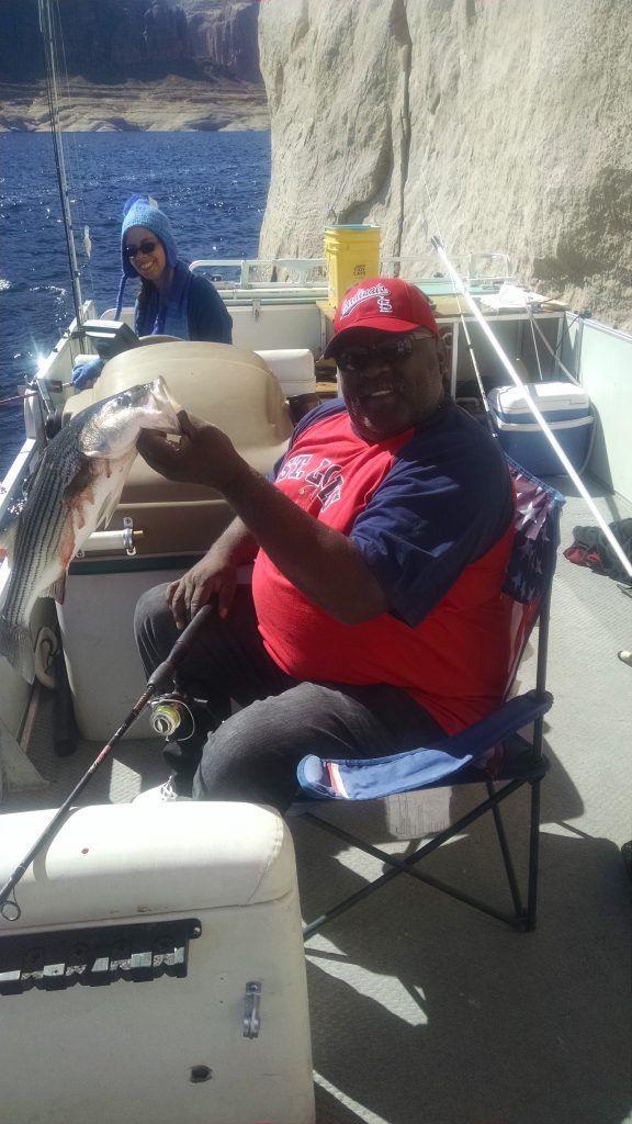 Image shows an angler proudly holding his freshly caught fish while on a fishing trip out at the lake.