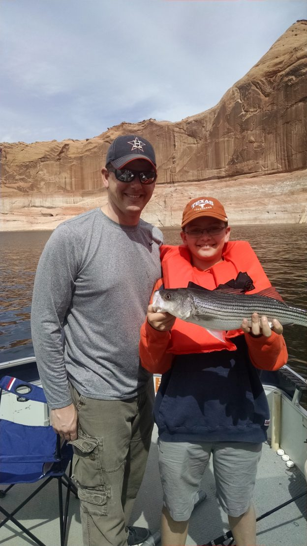 Image is of a father and his son holding their freshly caught fish while on a fishing trip at the lake.