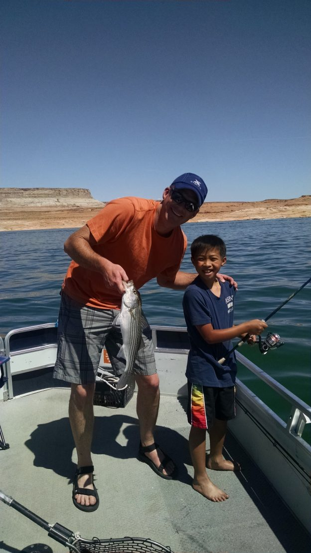 Image shows a young boy and a man holding a freshly caught fish on a sunny day, while fishing on the lake.