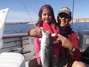 Her first catch - daughter and Dad with her first fish at Lake Powell, guided by Bill McBurney