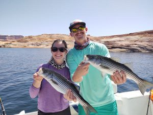 A couple from Boston hold up thier catches and smile broadly, they are fishing with Captain Bill of Ambassador Guides on Lake Powell, AZ