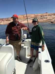 Virginia family enjoying fishing on Lake Powell - man and woman in a boat holding fishing rod and a landed stiper.