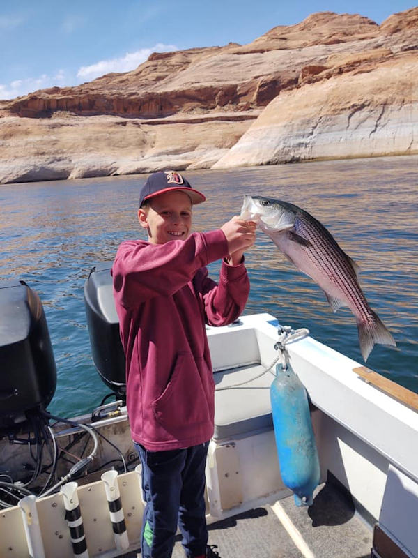 Young boy, Hank, holding up his Catch of the Day, a nice sized striped bass