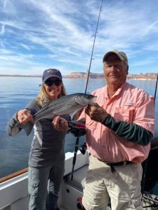 Spring Fishing starts on Lake Powell - Captain Bill McBurney and Guest holding a nice sized striper.